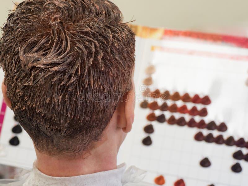Ein Mann beschließt Farbe, um sein Haar zu färben stockfoto