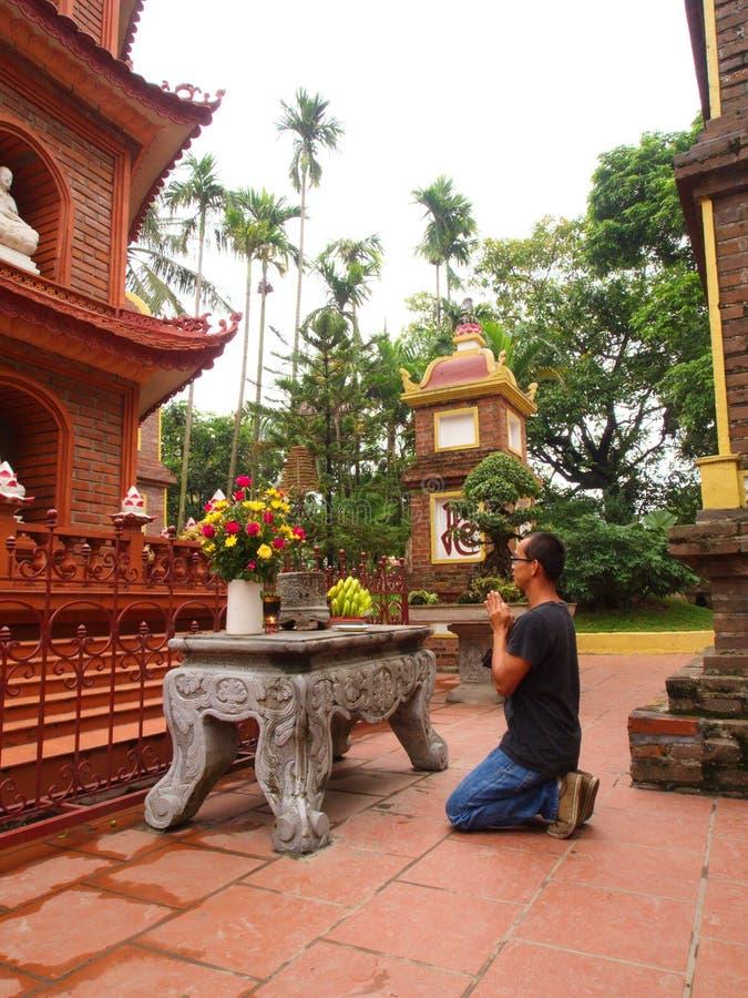 Ein Mann beten in chua tran quoc Tempel nahe Ho Tay Lake in Hanoi, V stockfotos
