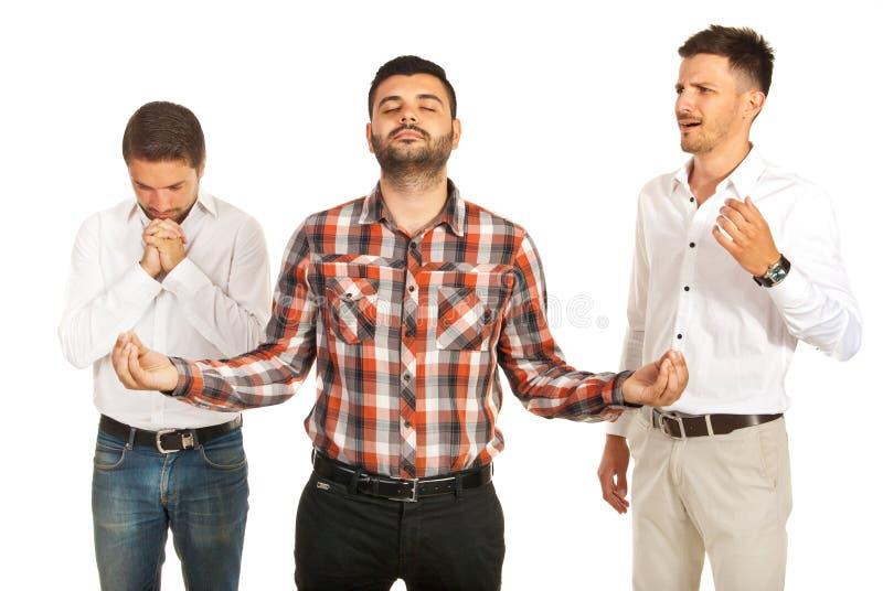 Ein Mann beten, meditieren anderer und ein anderer erschreckend lizenzfreie stockfotos