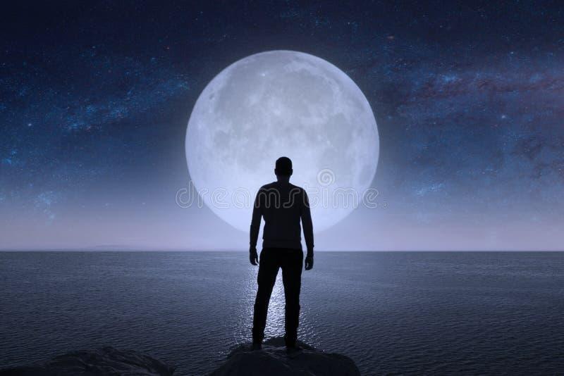 Ein Mann betrachtet die Sterne und den Mond lizenzfreie stockfotos