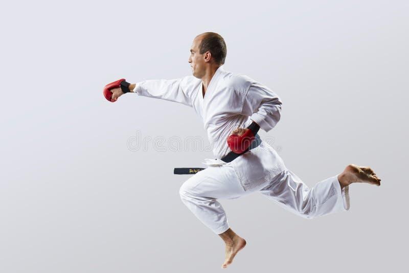 Ein Mann bildet einen Durchschlag mit einer Hand in einem Sprung gegen einen hellen Hintergrund aus stockfoto
