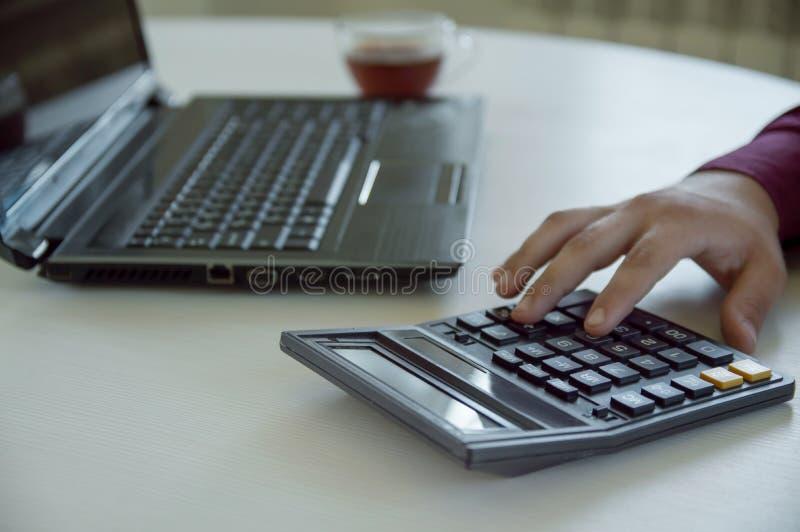 Ein Mann in den Arbeiten eines Büros hinter einem Laptop und in den Zählungen auf einem Taschenrechner Hand mit einem Rechner Ges stockfoto