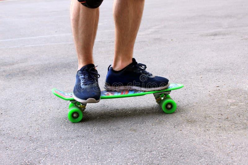 Ein Mann in den blauen Turnschuhen, die ein grünes Skateboard reiten lizenzfreies stockbild