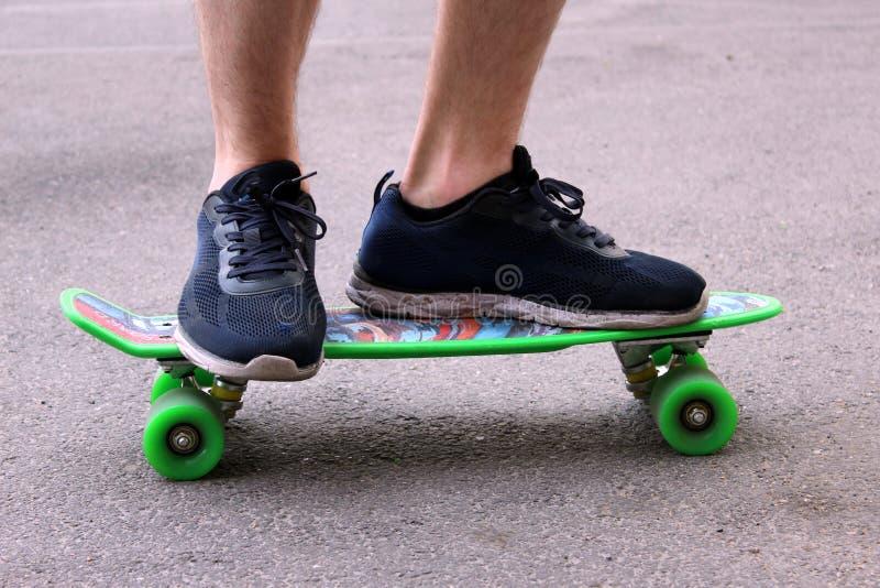 Ein Mann in den blauen Turnschuhen, die ein grünes Skateboard reiten lizenzfreie stockfotografie