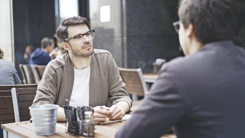 Ein Mann in den Brillen auf seinen Freund draußen hören am Café sprechend stockbild