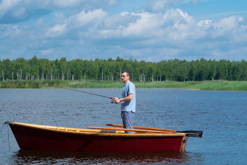 Ein Mann in den gelben Gläsern, auf einem Boot mit den Rudern, eine Angelrute halten und fischen mitten in dem See, gegen ein sch stockfotos