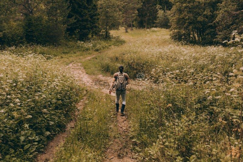 Ein Mann in den Gummistiefeln geht zurück durch eine Blumenwiese lizenzfreies stockfoto