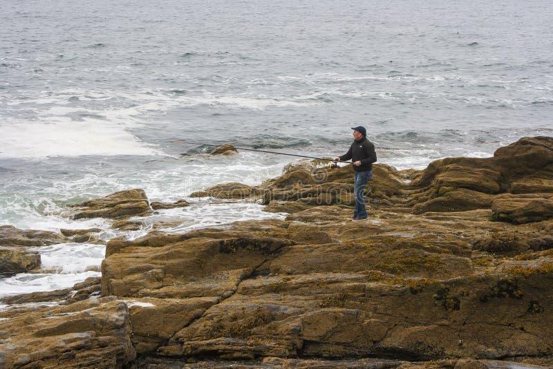 Ein Mann, der allein in Carlingford-Lough nahe Newcastle fischt stockbild