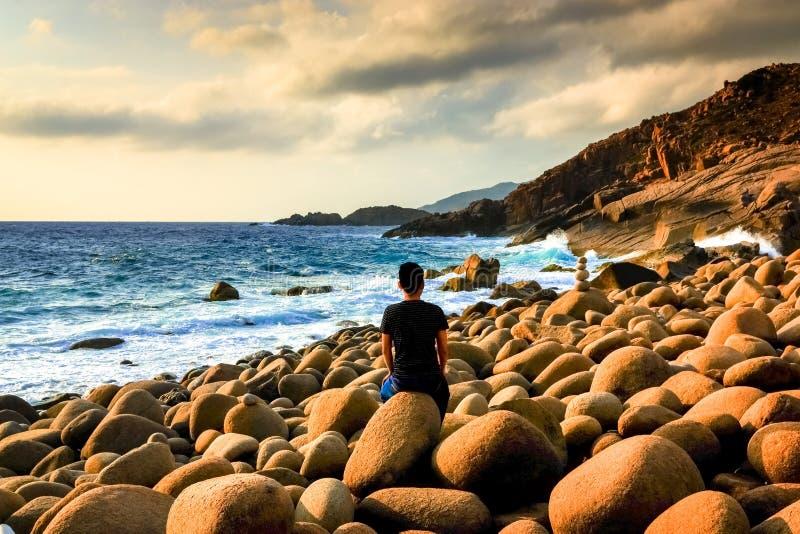 Ein Mann, der allein mit seinem Thoughs an wilde Eggshaped Felsen sitzt, setzen mit drastischen Wolken im Himmel auf den Strand lizenzfreie stockfotos