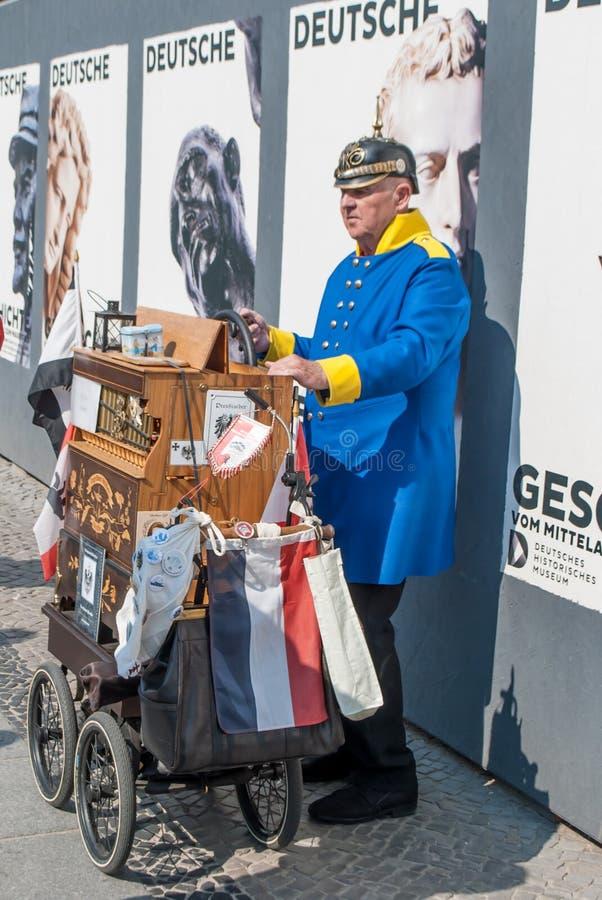 Ein Mann, in der alten Uniform eines deutschen Soldaten, die Drehorgel auf der Hauptstraße von Berlin spielend lizenzfreies stockfoto