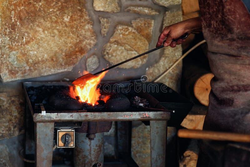 Ein Mann in der Arbeitskleidung arbeitet mit Metall Ein Mann h?lt einen Hammer und ein Blei in seiner Hand lizenzfreie stockfotos