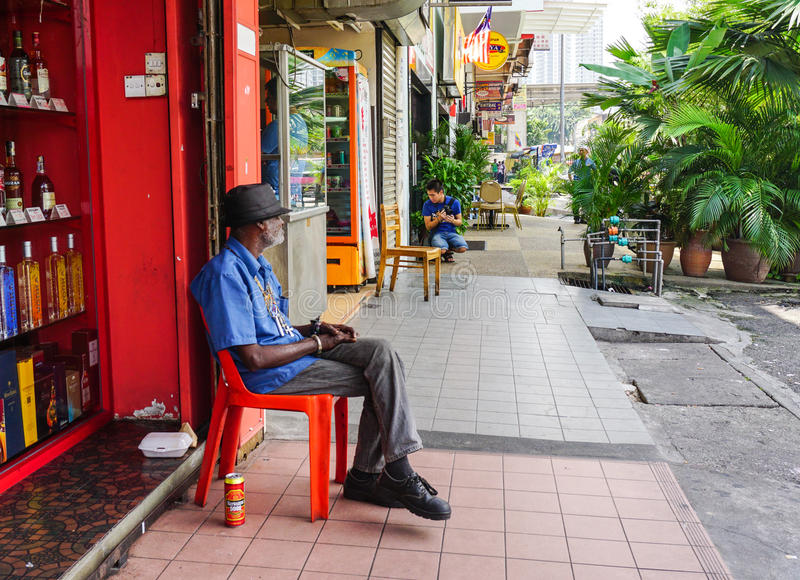 Ein Mann, der auf Straße in Cameron Highlands, Malaysia sitzt lizenzfreie stockfotos