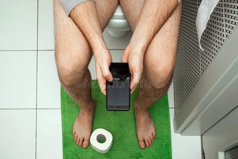 Ein Mann, der auf der Toilette hält einen Smartphone in seinen Händen, Draufsicht sitzt Das Konzept von Problemen mit dem Stuhl stockbild