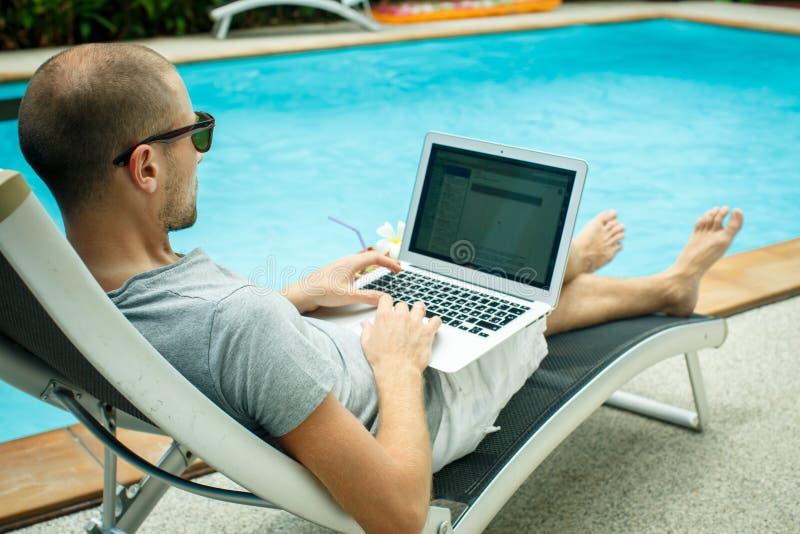 Ein Mann, der am Computer nahe bei dem Pool arbeitet lizenzfreie stockfotos