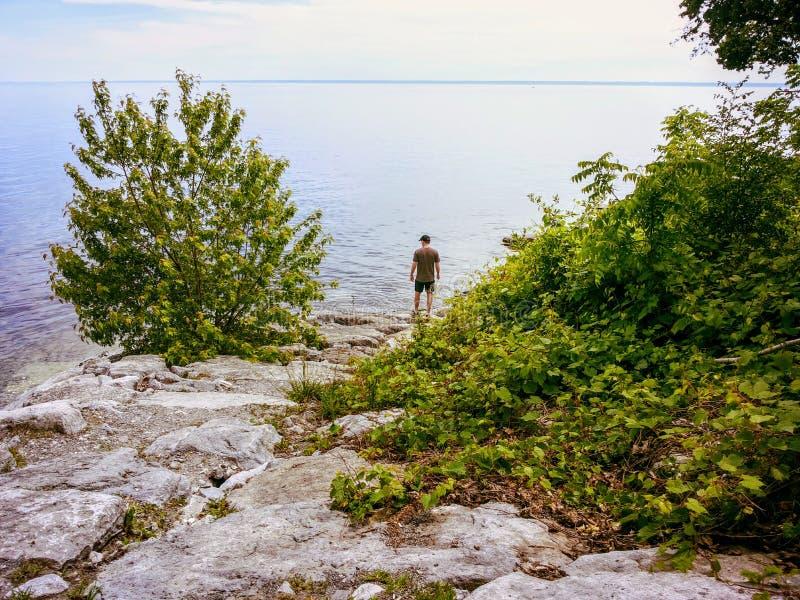 Ein Mann, der das Ufer vom Ontariosee in Oakville, Ontari, Kanada, heraus starrend entlang des beträchtlichen Wassers des großen  stockfotos