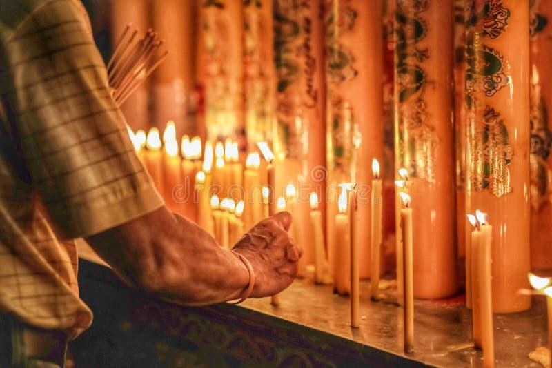 Ein Mann, der die Kerze am Tempel für heilige Sache der Anbetung beleuchtet lizenzfreies stockfoto