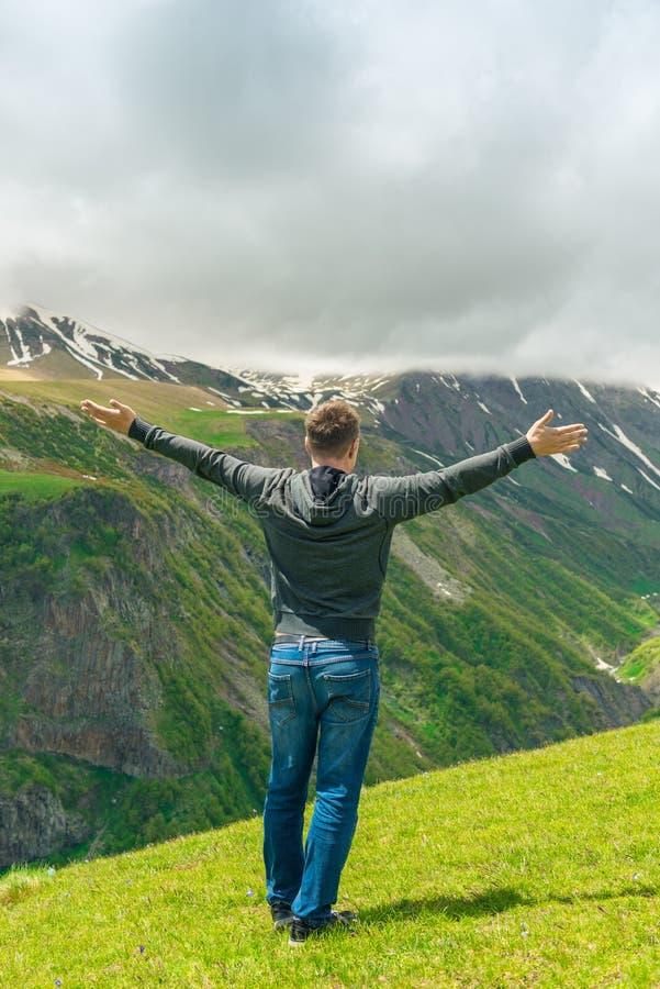 Ein Mann, der die schönen Bergspitzen bewundert, Ansicht von der Rückseite lizenzfreies stockbild