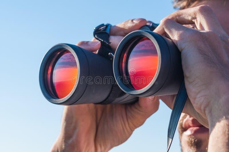 Ein Mann, der durch die Ferngläser schaut stockbild