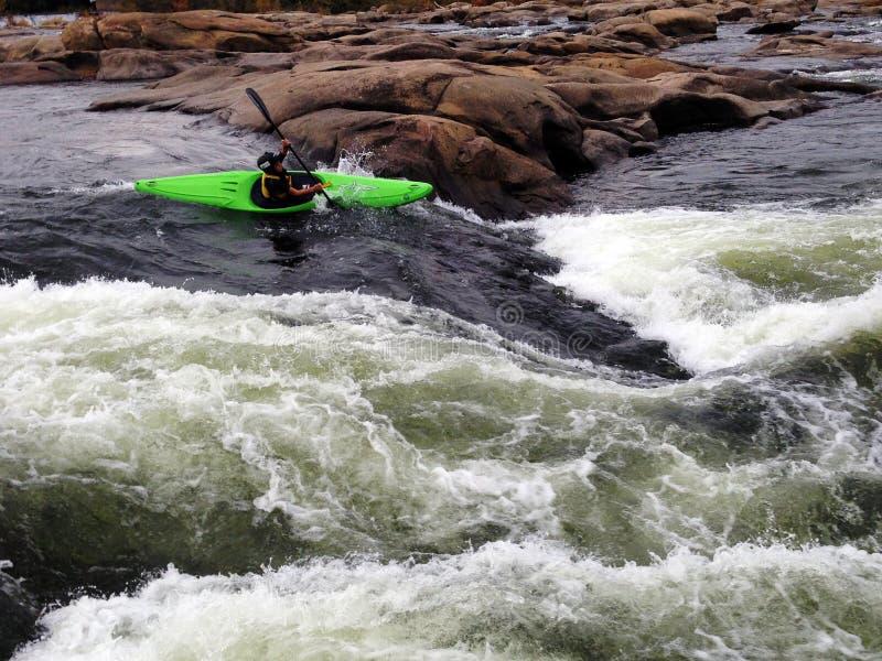 Ein Mann, der durch Flussstromschnellen im Whitewater Kayak fährt stockfoto