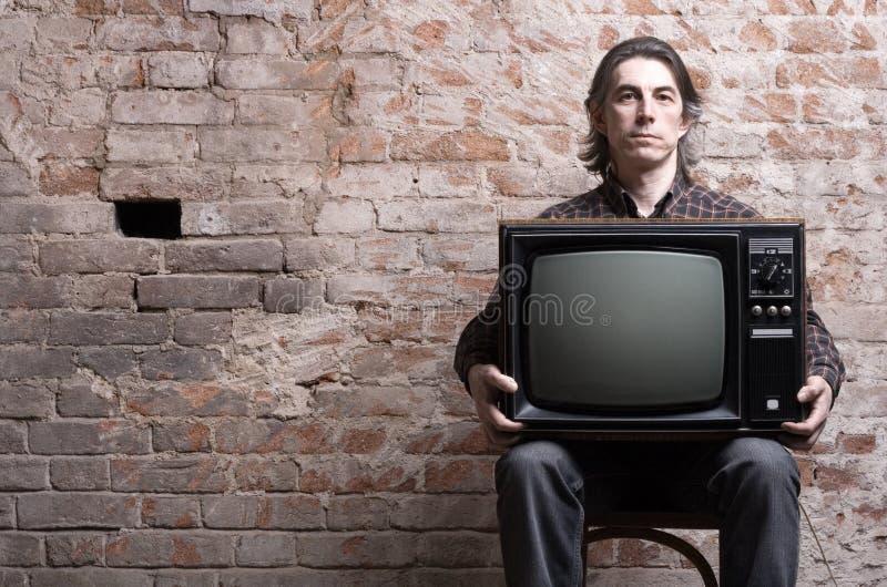 Ein Mann, der ein Retro- Fernsehen anhält lizenzfreie stockfotografie
