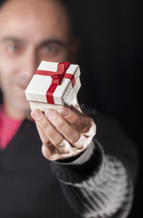 Ein Mann, der eine Geschenkbox hält, um zu geben lizenzfreie stockbilder