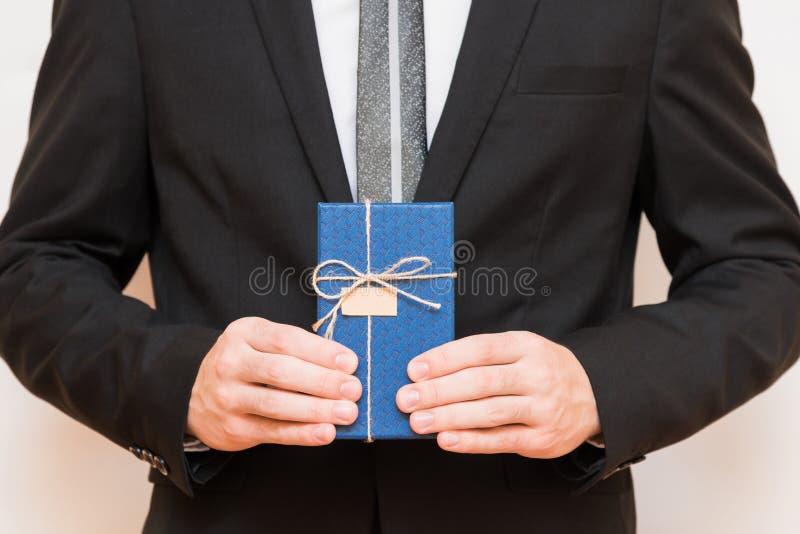 Ein Mann, der eine Geschenkbox in seinen Händen hält stockfoto