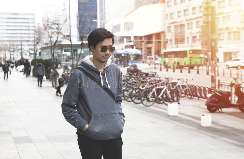 Ein Mann, der eine graue Strickjacke geht auf eine Stra?e in einer Stadt im Winter tr?gt stockfotos