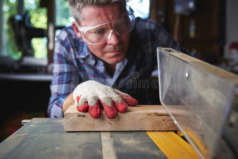 Ein Mann, der eine Tabellensäge verwendet lizenzfreie stockfotos