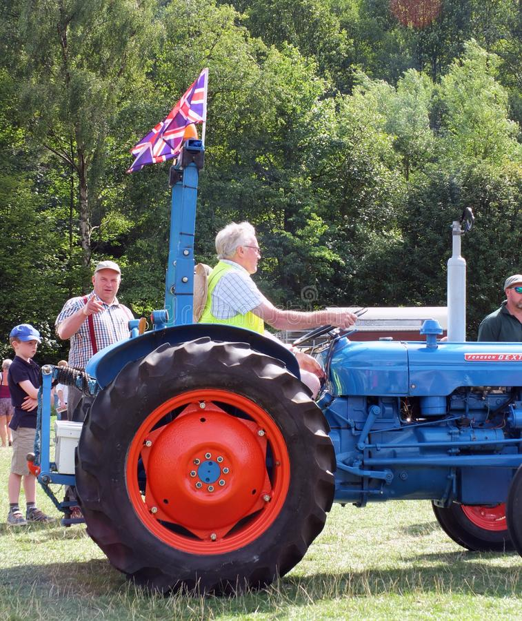 Ein Mann, der einen alten britischen Traktor mit Union Jack an fährt, hebden allgemeine Fahrzeugshow des Brückenweinlesewochenend lizenzfreies stockfoto