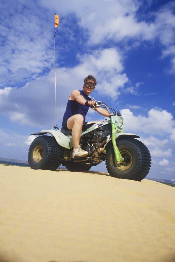 Ein Mann, der einen dreirädrigen Geländewagen in kleiner Sahara State Park, Oklahoma reitet stockbild