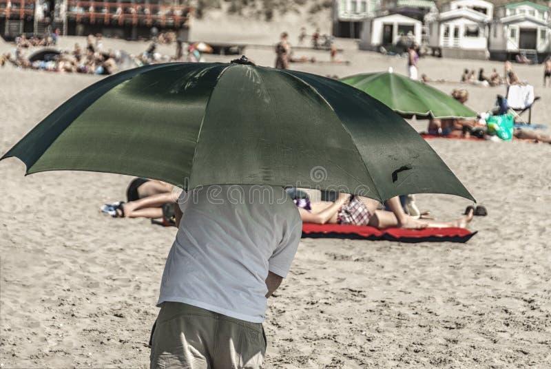 Ein Mann, der einen grünen Regenschirm hält stockbild