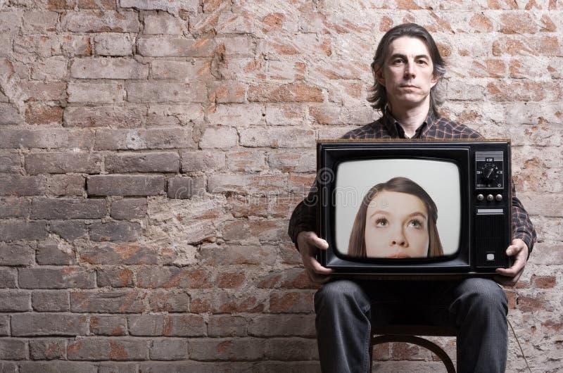 Ein Mann, der einen Retro- Fernsehapparat anhält stockbild