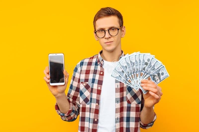 Ein Mann, der Gläser und ein kariertes Hemd trägt, zeigt seinen Bargeldpreis und einen leeren Bildschirm eines Smartphone, auf ei lizenzfreie stockfotografie