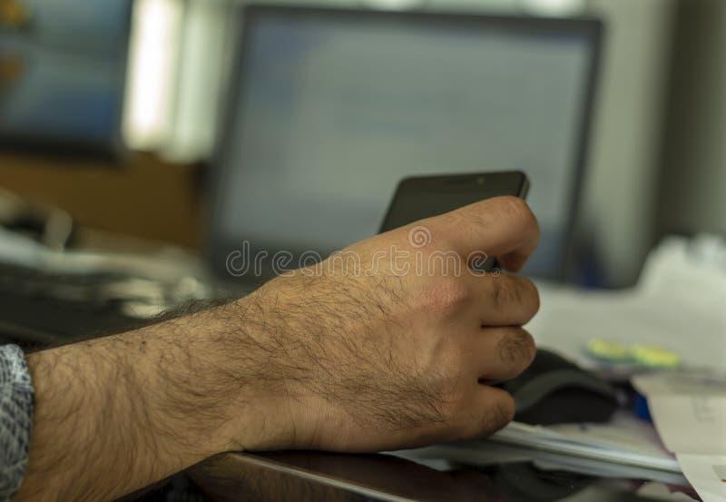 Ein Mann, der ihn Handy behandelt lizenzfreies stockbild