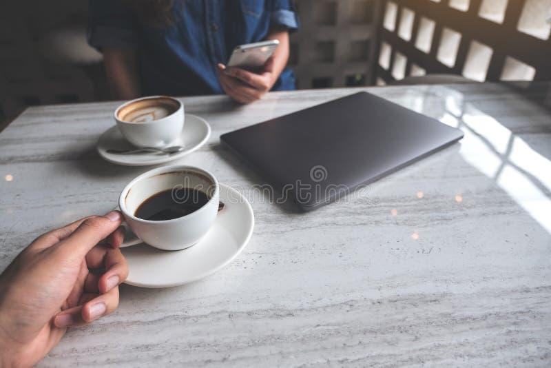 Ein Mann, der Kaffeetasse halten und eine Frau, die Smartphone mit Laptop auf Tabelle im Café verwendet stockbilder