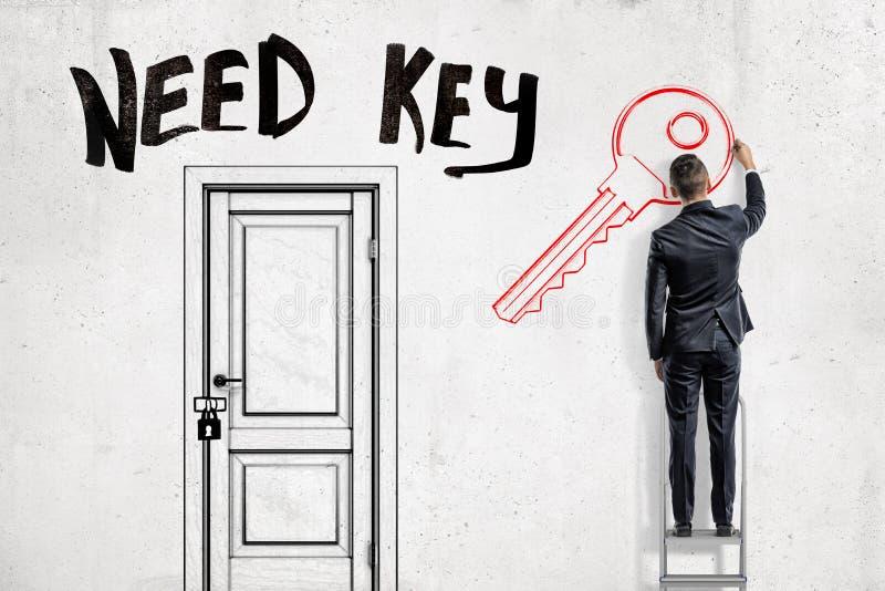 Ein Mann in der Klage, die auf einer Leiter auf der rechten Seite einer verschlossenen Tür mit dem Titel 'Bedarfs-Schlüssel 'oben stockfotografie