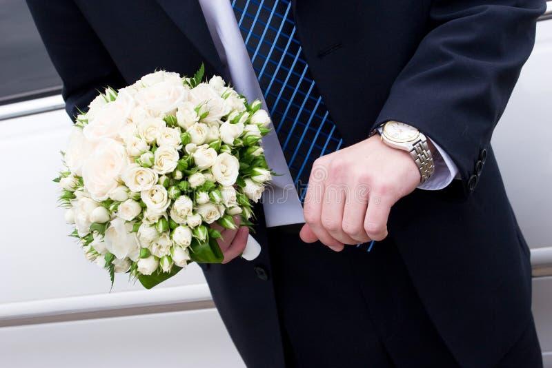 Ein Mann in der Klage mit Uhr handsand ein Blumenblumenstrauß lizenzfreies stockbild