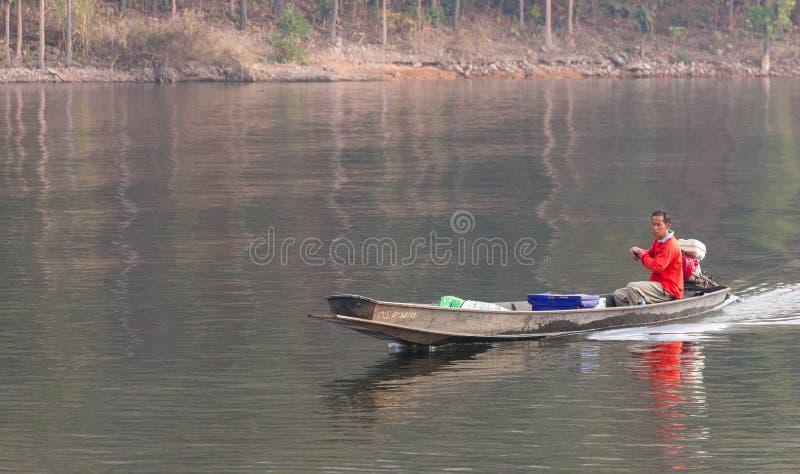 Ein Mann, der ein lokales kleines Boot hergestellt vom Eisen fährt stockbild