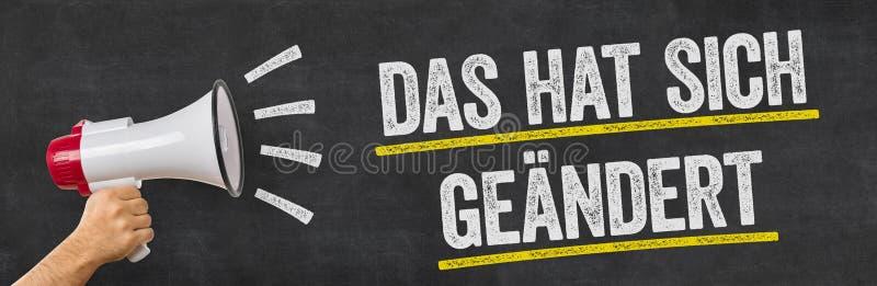 Ein Mann, der ein Megaphon hält - deutsche Übersetzung von diesem hat geändert - DAS-Hut sich geaendert stockfotografie