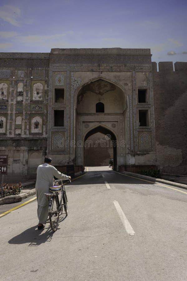 Ein Mann, der mit seinem Fahrrad vor einem Eingang von Lahore-Fort geht, lizenzfreies stockfoto