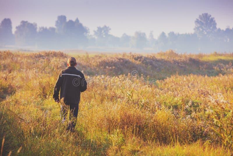 Ein Mann, der morgens durch das Feld geht stockbild