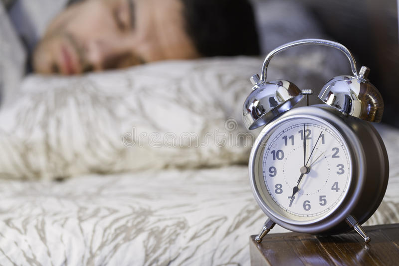 Ein Mann, der nah an einer Retro- Alarmuhr schläft lizenzfreie stockfotografie