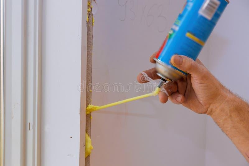 Ein Mann, der Polyurethanschaum verwendet, um ein Fenster auf einem gut aussehenden Arbeiter in Aktion zu installieren lizenzfreies stockbild