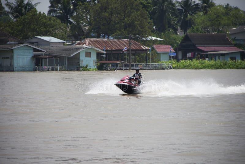 Ein Mann, der rote Jet Ski reiten und Spritzen wässern in der Mitte von Fluss lizenzfreie stockfotos