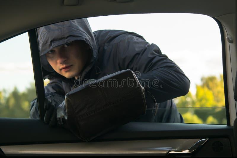 Ein Mann in der schwarzen Kleidung mit einer Haube, begeht ein Verbrechen, nimmt eine Tasche durch das Autofenster stockbild