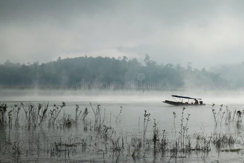 Ein Mann, der sein Boot in Sangkhlaburi, Thailand rudert lizenzfreies stockbild
