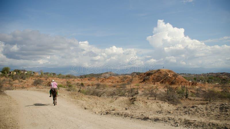 Ein Mann, der sein Pferd in der Tatacora-Wüste, Kolumbien reitet lizenzfreie stockfotos