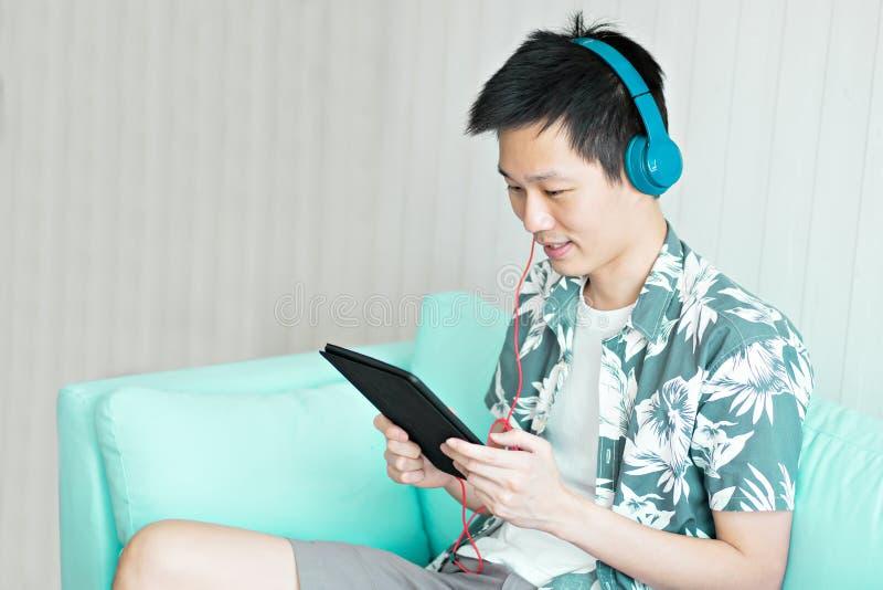 Ein Mann, der Tablette mit Kopfhörern für hält, hören Musik lizenzfreie stockfotografie