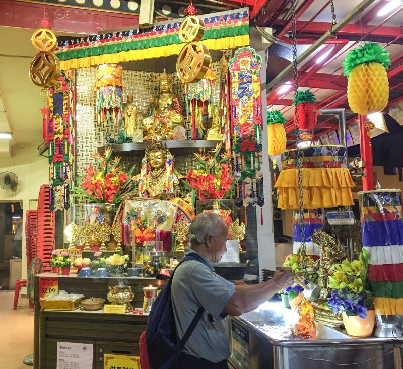 Ein Mann, der am tibetanischen Tempel in Singapur betet lizenzfreie stockfotografie