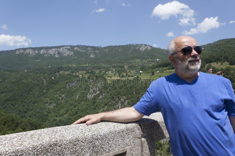 Ein Mann der tragenden Sonnenbrille des reifen Alters, kahl, mit einem Bart auf Th lizenzfreies stockbild